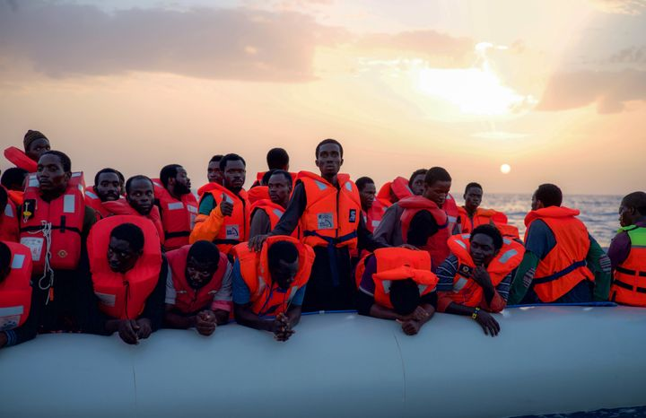 Migrants await rescue after receiving life jackets from the <em>Minden</em> aid ship 18 miles off the Libyan coast.