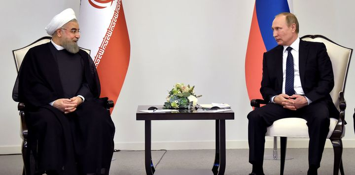 Iranian President Hassan Rouhani talks to Russian President Vladimir Putin during a meeting in Baku, Azerbaijan on August 8 2