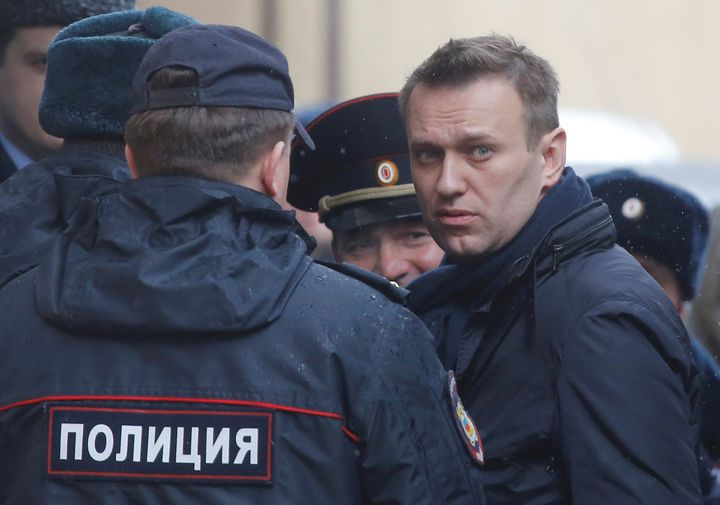 Russian opposition leader Alexei Navalny is escorted upon his arrival for a hearing after being detained at the protest again