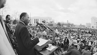 Dr. Martin Luther King, Jr. speaks from a platform on the street in front of the Alabama State Capitol, addressing an estimated 30,000 civil rights demonstrators who followed him on the last leg of the Selma-Mongomery Civil Rights Marches on March 25, 1965.