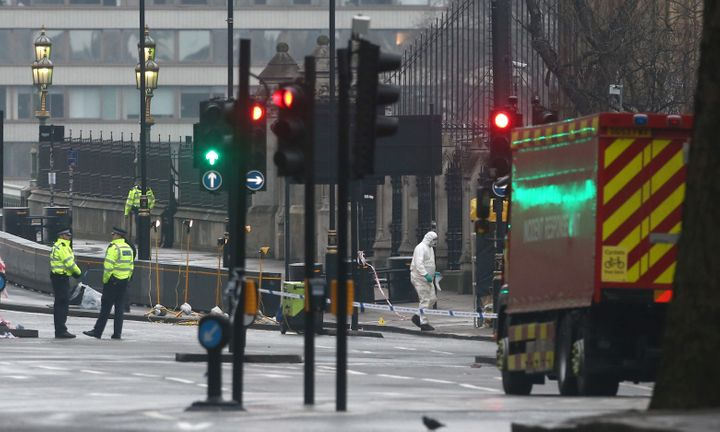 Forensics investigators and police officers work at the site near Westminster Bridge the morning after an attack by a man dri