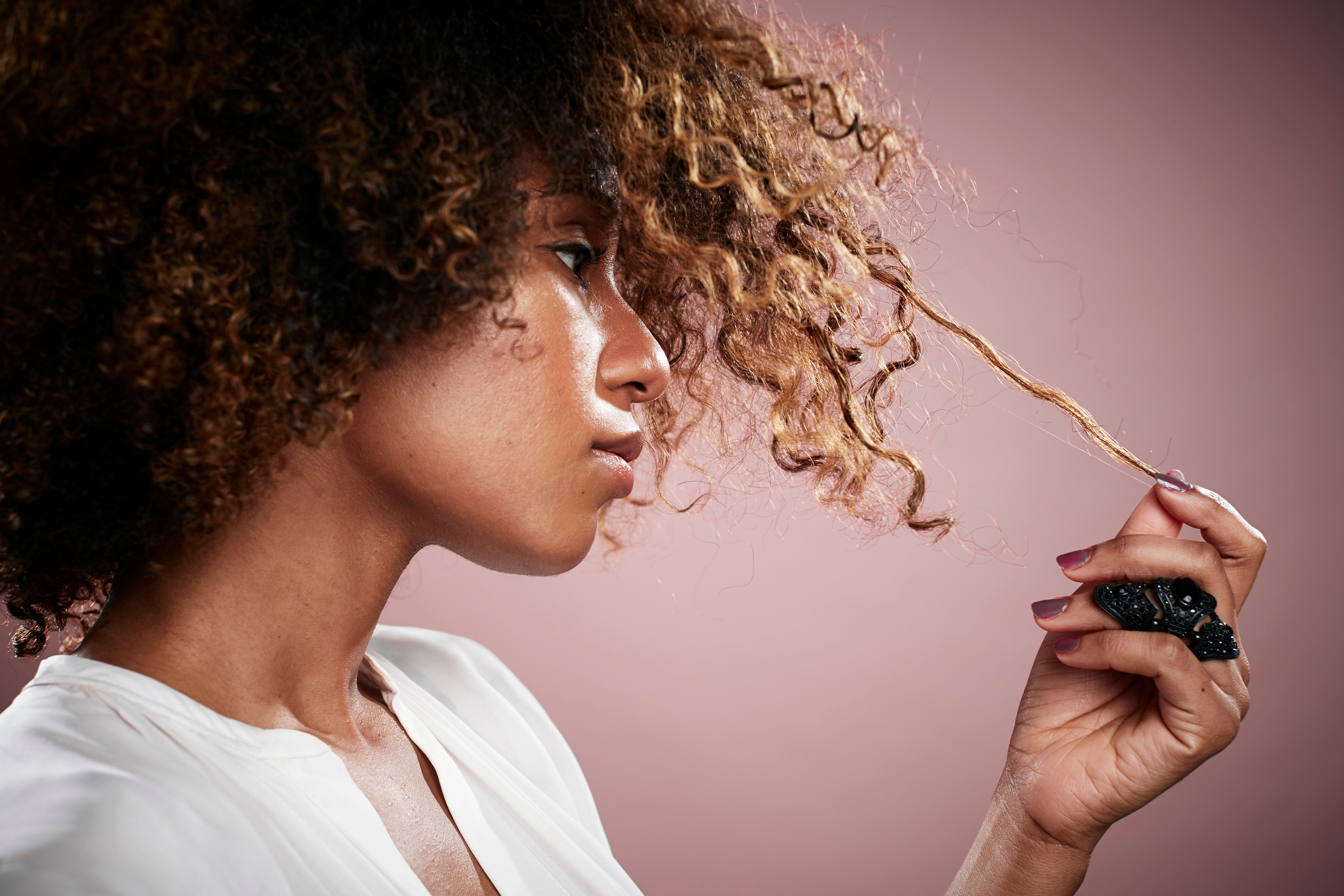 Portrait of young woman pulling on strand of curly hair