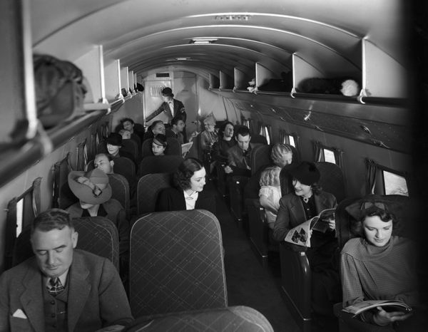 Passengers sitting in their seats inside the cabin of a 21-passenger airplane making daily trips between New York City and Ch