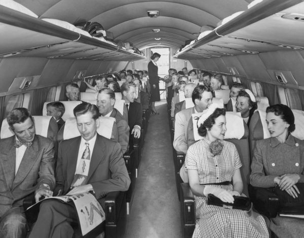 Passengers, seated two to a row, talk with their inflight neighbors aboard a Mainliner Convair aircraft as the flight attenda
