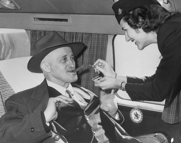 Stewardess Jane Driscoll lights a cigar for airline passenger Carl Graulein, 68, of East St. Louis, as he prepares to depart