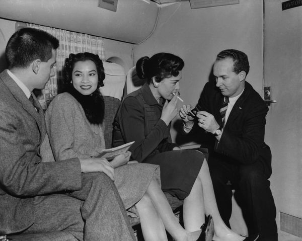 Passengers enjoy a relaxing smoke on a Transocean Air lines Boeing 377 Stratocruiser circa 1955.