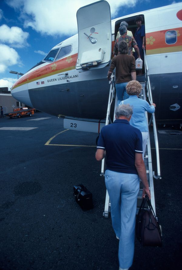 Passengers board an Aloha Airlines plane named after Hawaiian monarch 'Queen Liliuokalani' at Honolulu airport in Honolu