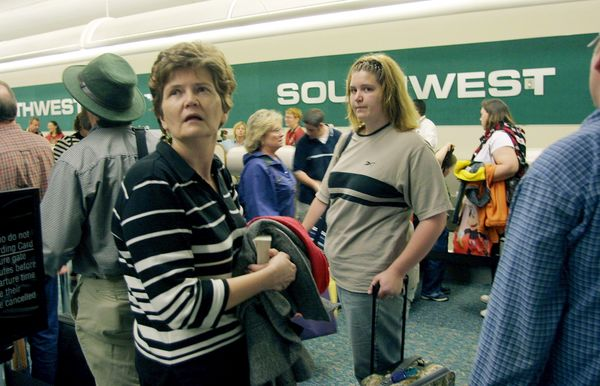 Passengers wait in line at the low-cost carrier Southwest Airlines ticket counter at Orlando International Airport in Or