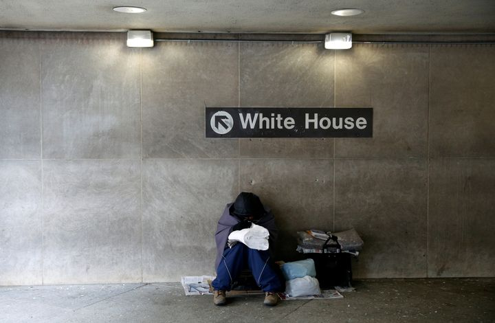 On an unseasonably cold day, a homeless person tries to stay warm at the entrance of a subway station near the White House in