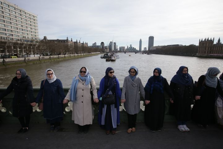 Women activists wearing blue hold hands on Westminster Bridge in front of the Houses of Parliament to honour the victims of t