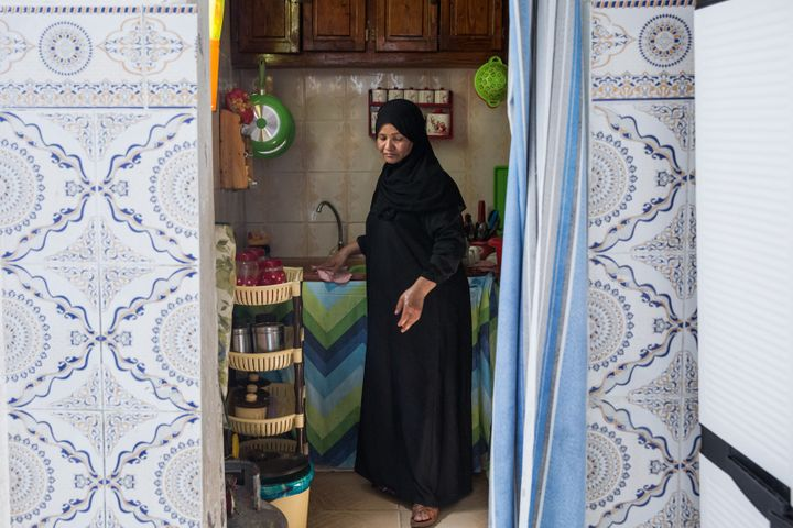 Naziha Bel Jayyed, the mother of a former fighter, washes dishes in her home in a suburb in northwest Tunis.