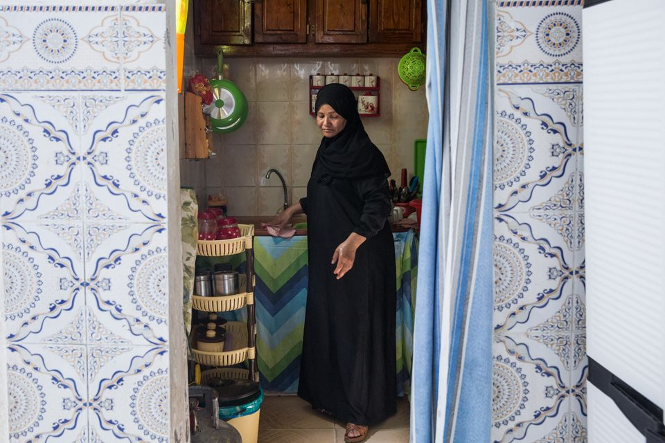 Naziha Bel Jayyed, the mother of a former fighter, washes dishes in her home in a suburb in northwest