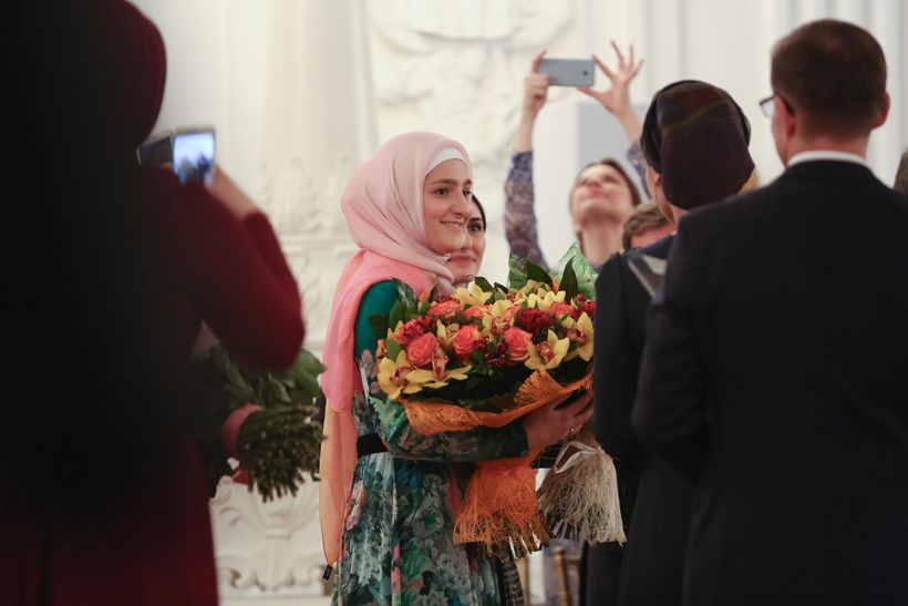 Firdaws designer Aishat Kadyrova accepts bouquets of flowers after runway presentation