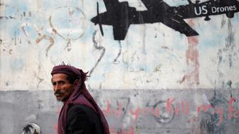 A man walks past a graffiti, denouncing strikes by U.S. drones in Yemen, painted on a wall in Sanaa, Yemen February 6, 2017. Picture taken February 6, 2017.  REUTERS/Khaled Abdullah