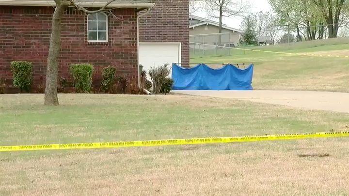 A blue tarp covers part of the scene of Monday's deadly shooting outside Broken Arrow, Oklahoma. Authorities said two of the