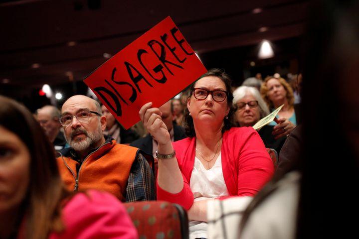 Elizabeth Lewandowski holds a sign as U.S. Congressman Leonard Lance (R-N.J.) hosts a town hall event at a community college