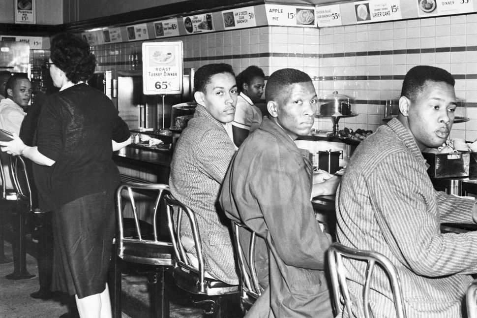 African-American students at North Carolina A&T College participate in a sit-in at a F. W. Woolworth's lunch counter rese
