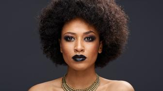 Beautiful exotic African American woman with a curly afro hairstyle wearing dark makeup and a gold choker looking directly at the camera with a serious thoughtful expression