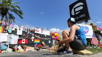 On the eve of the one-month anniversary of the Pulse nightclub massacre, a friend of two of the victims places flowers as visitors continue to flock to the club to their pay their respects on Monday, July 11, 2016 in Orlando. 49 people were shot and killed at the club on June 12.  (Joe Burbank/Orlando Sentinel/TNS via Getty Images)