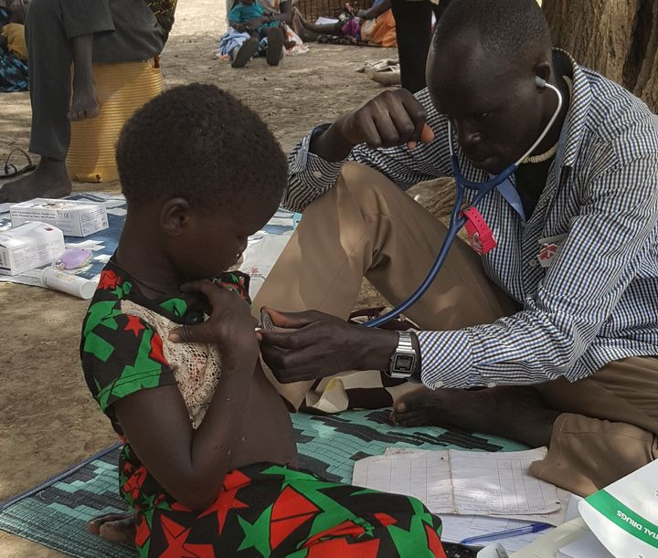 An MSF community health worker examines a 4-year-old girl suffering from malnutrition.