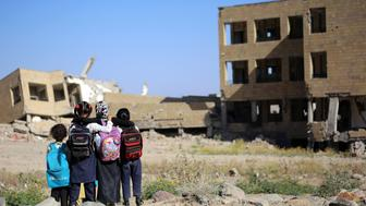 TOPSHOT - Yemeni school girls look at a school on March 16, 2017, that was damaged in an air strike in the southern Yemeni city of Taez.  The conflict in Yemen, which escalated with the intervention of the Saudi-led coalition two years ago, has more than doubled the number of children deprived of schooling to some 3.5 million, threatening the future of a whole generation in the impoverished country. / AFP PHOTO / Ahmad AL-BASHA        (Photo credit should read AHMAD AL-BASHA/AFP/Getty Images)