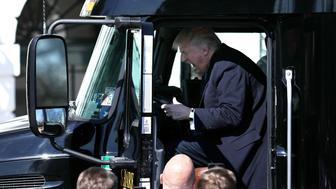 U.S. President Donald Trump reacts as he sits on a truck while he welcomes truckers and CEOs to attend a meeting regarding healthcare at the White House in Washington, U.S., March 23, 2017.  REUTERS/Carlos Barria