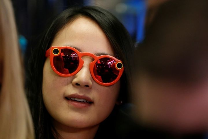 A woman wears Snapchat Spectacles on the floor of the New York Stock Exchange, on March 2, 2017.