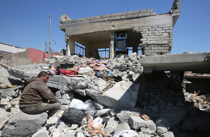 An Iraqi man sits amid the rubble of destroyed houses in the Mosul al-Jadida area on March 26, 2017, following air strikes in