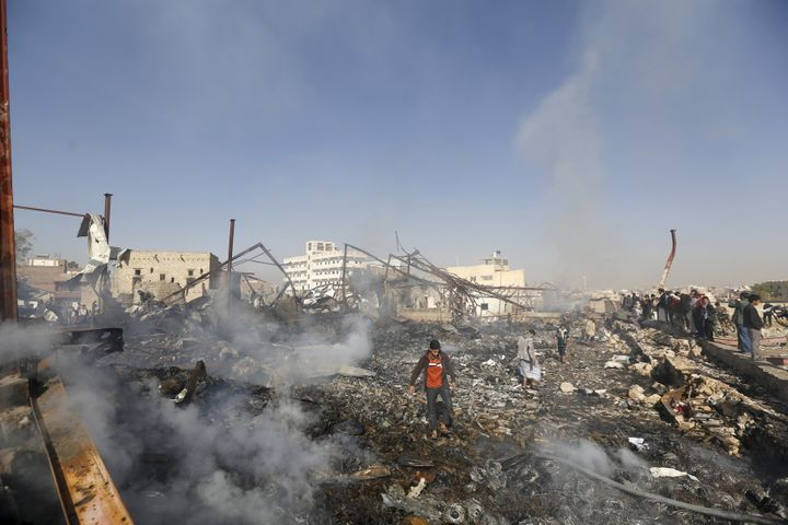 People walk on the rubble of an electronics warehouse store after a Saudi-led airstrike destroyed it in Yemen's capital of Sa