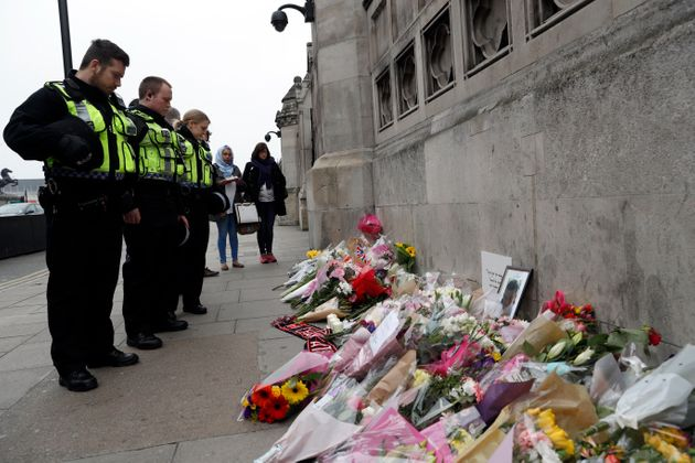 Police officers and civilians look at floral tributes near Westminster Bridge following a recent attack...