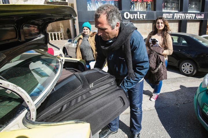 Faraj Ghazi al-Jamous, a Syrian refugee, loads his family's luggage into a taxi after departing from a hotel they had stayed