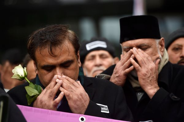 Muslim men pray at the memorial vigil.