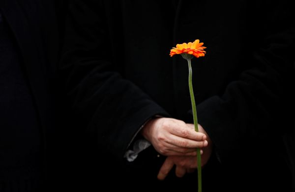 A Muslim man holds a flower as he stands in line with others on Westminster Bridge.