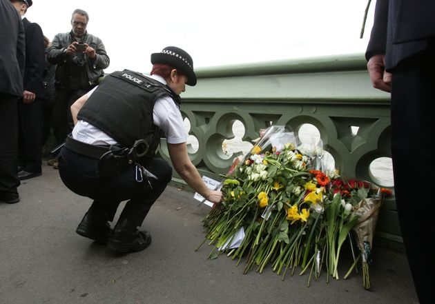 A police office lays flowers at a vigil held on Westminster Bridge in