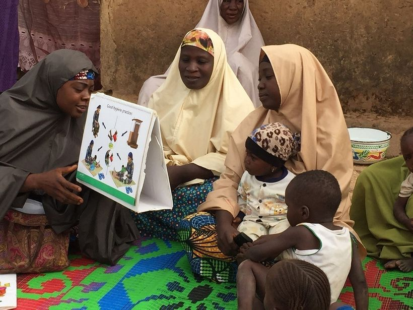 <em>A community volunteer in Nigeria discusses the introduction of complementary foods to children at six months of age.</em>