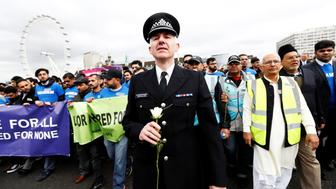 A police officer holds a flower as he joins people on Westminster Bridge during an event to mark one week since a man drove his car into pedestrians then stabbed a police officer in London, Britain, March 29, 2017. REUTERS/Stefan Wermuth         TPX IMAGES OF THE DAY