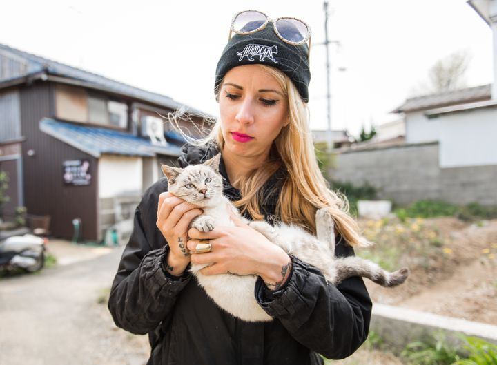 Cat rescuer and advocate Hannah Shaw holds a young cat on Ainoshima.