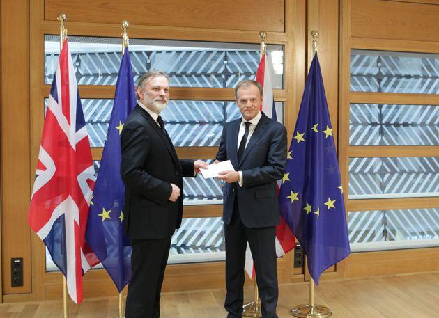 Britain's EU ambassador Sir Tim Barrow hands the letter to Donald