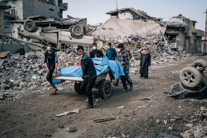 Local volunteers carry the bodies of civilians found in the rubble of a building in the Mosul al Jadidah neighborhood of Mosu