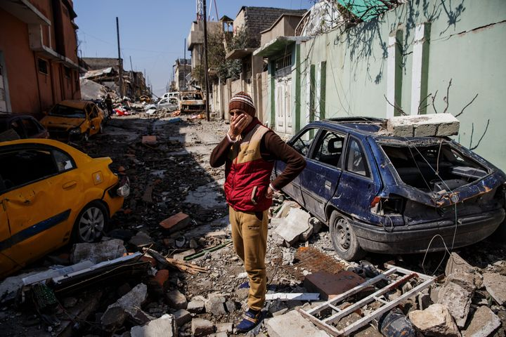Neighbors cover their faces because of the smell of corpses in the Mosul al-Jadida neighborhood of Mosul.