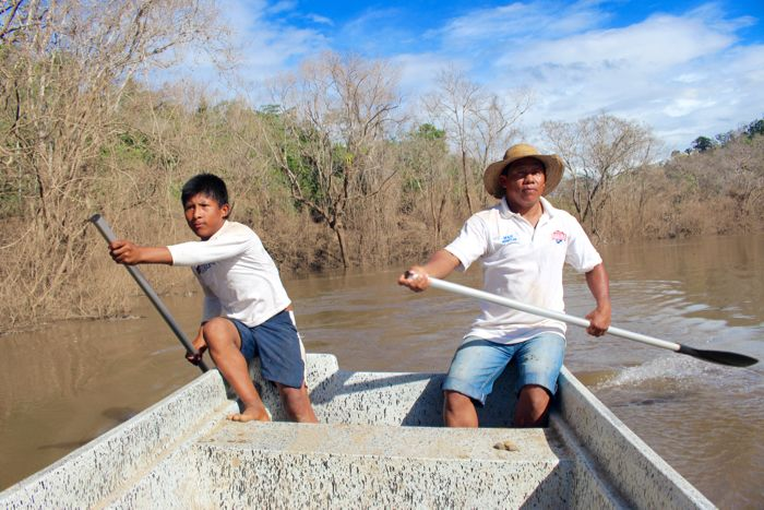 <em>Döegeo Gallardo and Göejet Miranda paddle home through the dead zone that was once a shady, fish-filled river. (Tracy L.