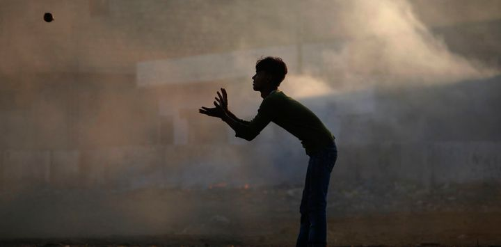 A boy silhouetted against smog while playing cricket in Karachi, Pakistan, in 2011.