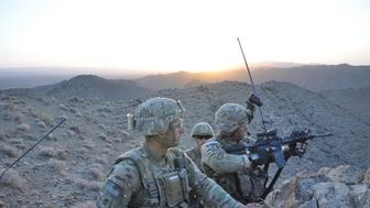 DAWAZAGAI, AFGHANISTAN  - JUNE 22: Staff Sgt. Joshua Devomendoza, 25, of Winton, Ca., left, looks for suspected Taliban fighters down a valley as his platoon commander, Lt. John Eife, 25, of West Chester, Pa., uses his rifle scope scan the landscape.  (Photo by Ernesto Londoño/The Washington Post via Getty Images)