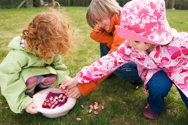 3 children in garden with Easter eggs Pascal Broze via Getty Images