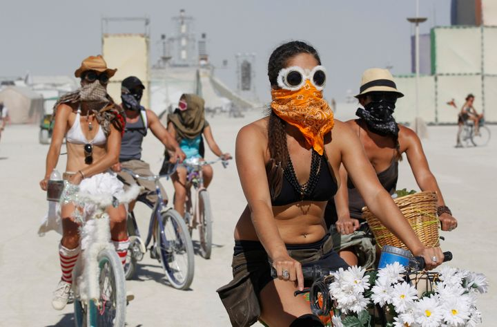 Participants wear face masks and goggles to protect themselves during a dust storm in the midst of the Burning Man.