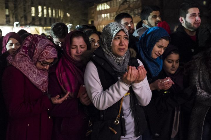 Friends and family pray at a vigil for three Muslims who were shot dead in Chapel Hill, North Carolina.