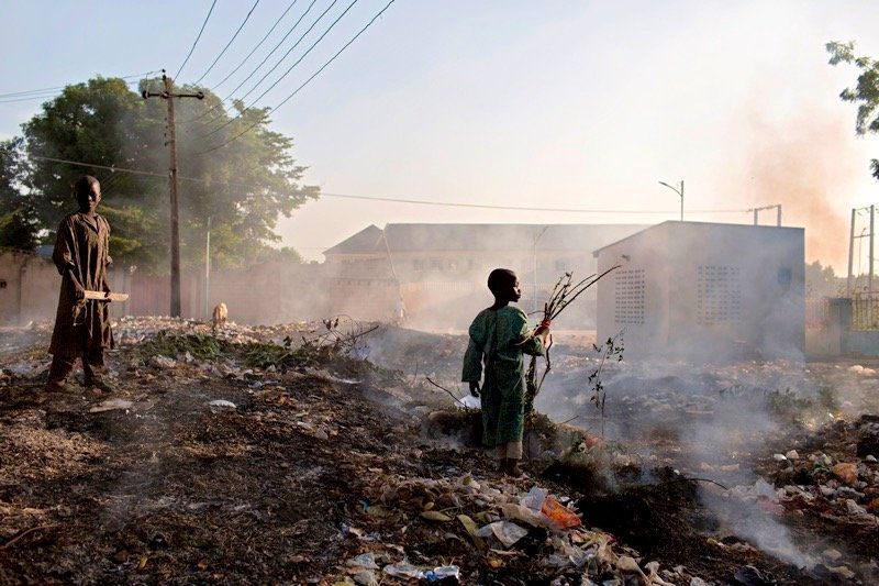 Young boys collect wood from a trash pile that is being burned in Maiduguri, Nigeria.