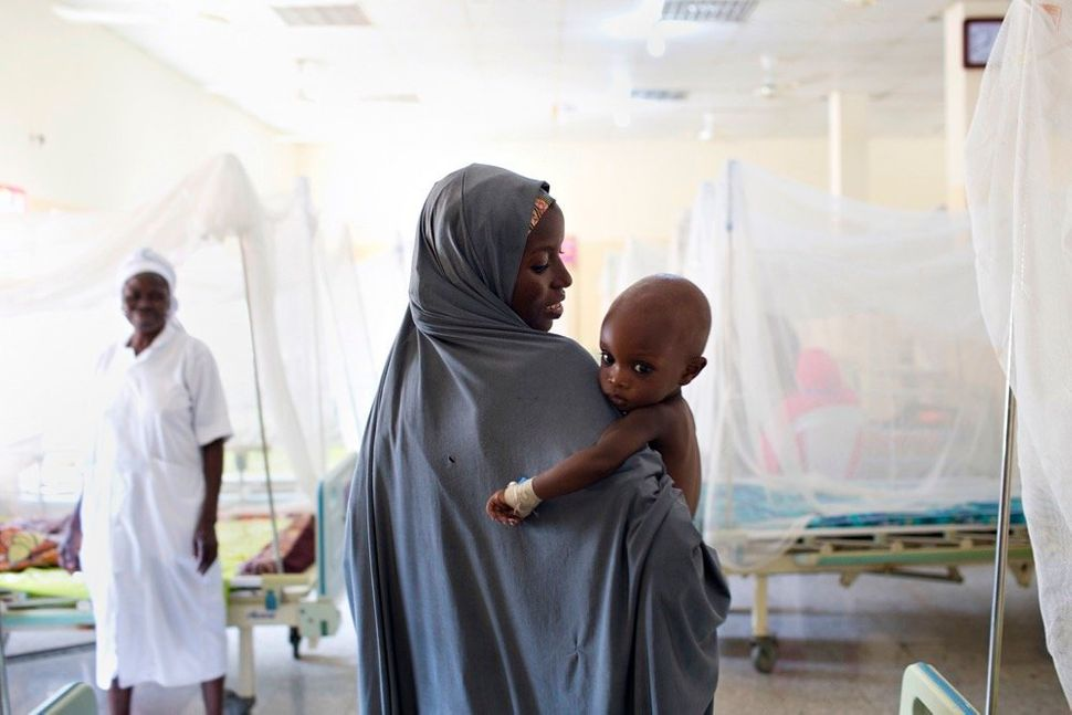 A mother carries her child, who suffers from severe acute malnutrition, through an inpatient stabilization center run by the
