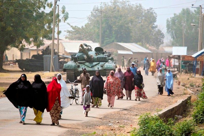 People walk towards the location of a food distribution in Michika, a town formerly occupied by Boko Haram, on Feb. 20, 2016.