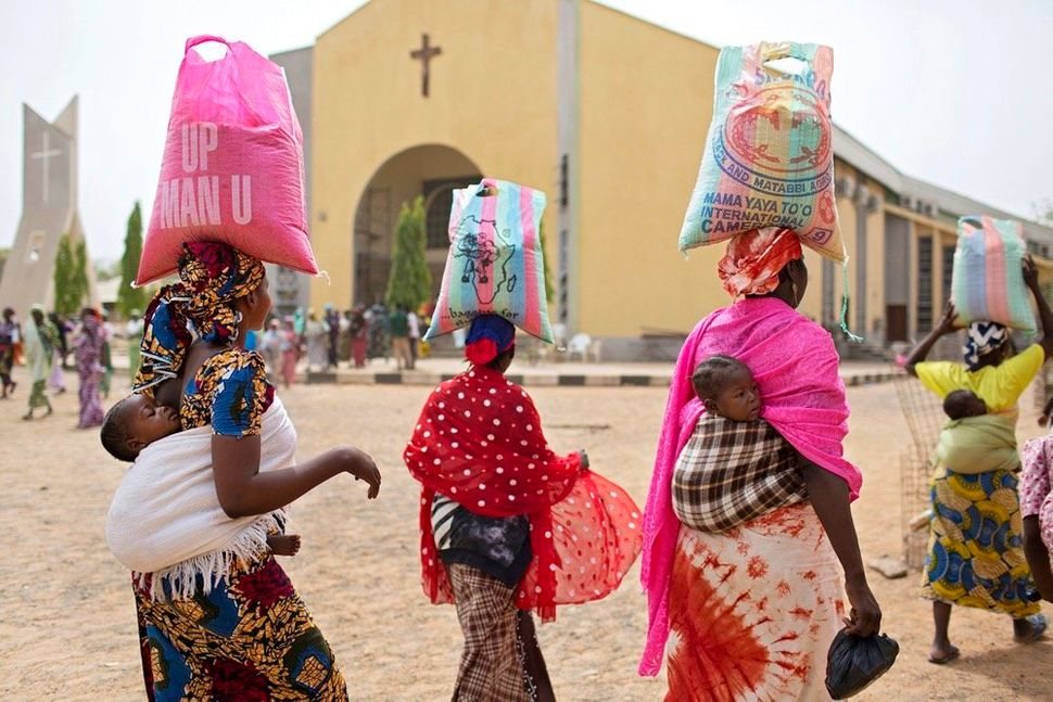 Women leave a food distribution hosted by St. Theresa's Cathedral on March 21, 2016, in Yola, a city in northeastern Ni